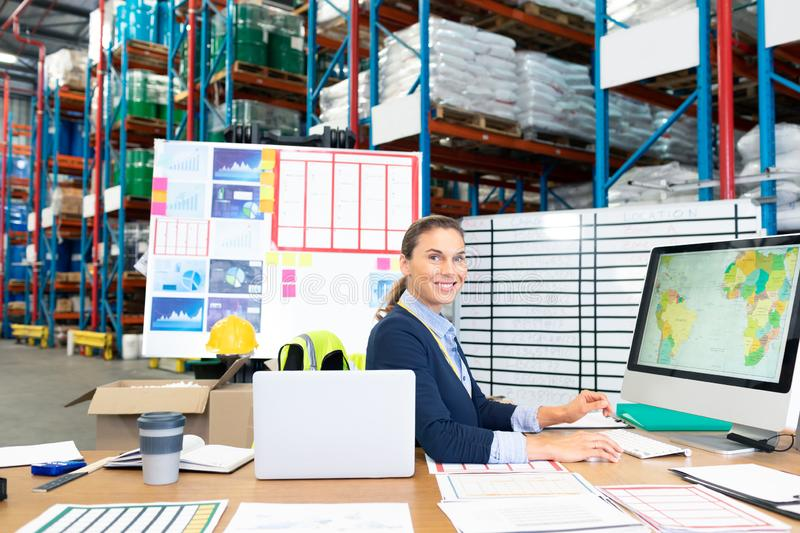 Female manager working on computer at desk in warehouse. Portrait of beautiful Caucasian female manager working on computer at desk in warehouse. This is a stock images