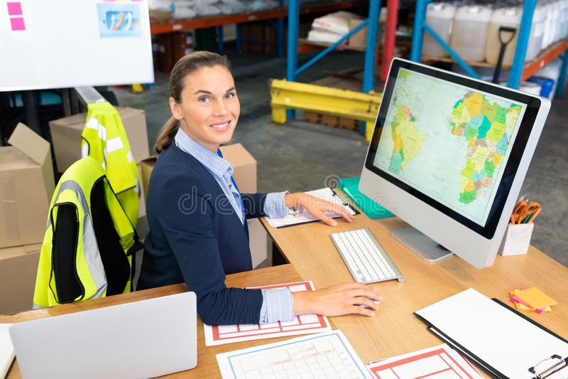 Female manager working on computer at desk in warehouse. Portrait of beautiful young Caucasian female manager working on computer at desk in warehouse. This is a royalty free stock photo
