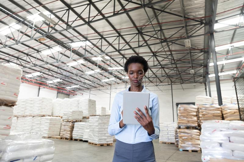 Female manager working on digital tablet in warehouse. Front view of female manager working on digital tablet in warehouse. This is a freight transportation and stock images