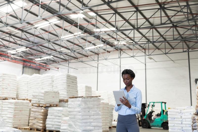 Female manager working on digital tablet in warehouse. Front view of female manager working on digital tablet in warehouse. This is a freight transportation and royalty free stock image