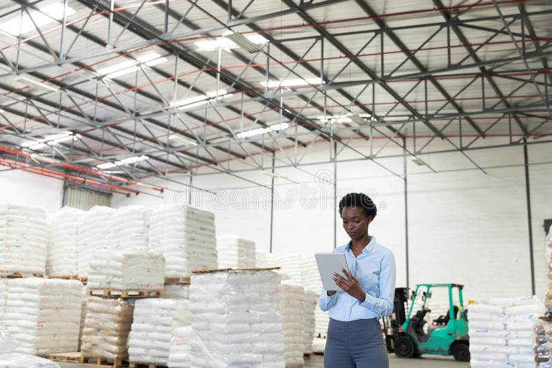 Female manager working on digital tablet in warehouse. Front view of female manager working on digital tablet in warehouse. This is a freight transportation and royalty free stock images