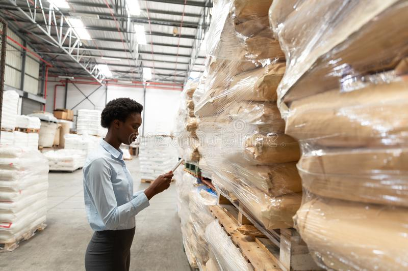 Female manager working on digital tablet in warehouse. Side view of female manager working on digital tablet in warehouse. This is a freight transportation and stock image