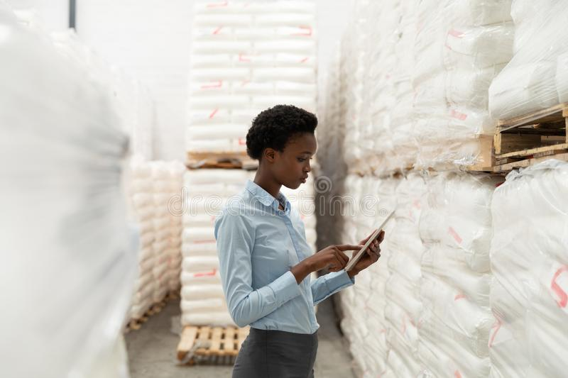 Female manager working on digital tablet in warehouse. Side view of female manager working on digital tablet in warehouse. This is a freight transportation and stock photo