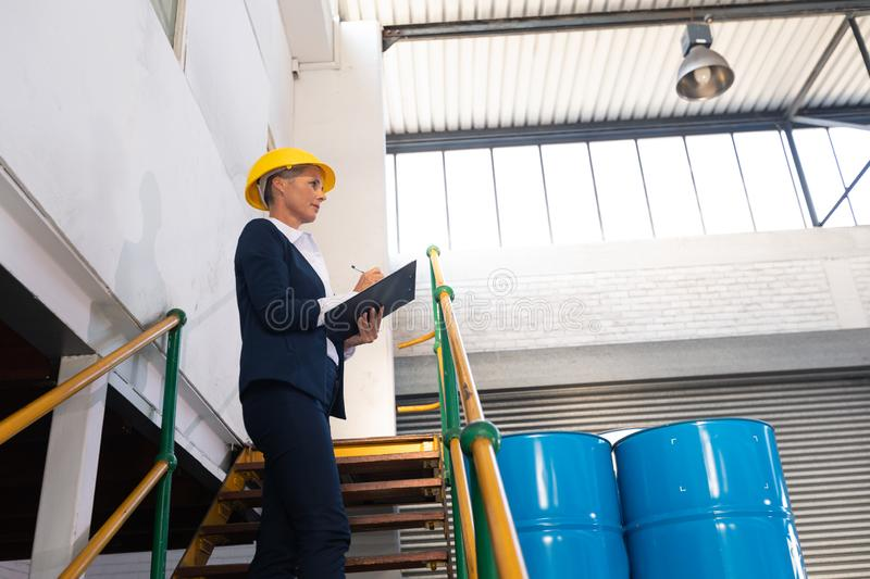 Female manager writing on clipboard on stairs in warehouse. Low angle view of Caucasian female manager writing on clipboard on stairs in warehouse. This is a stock photography