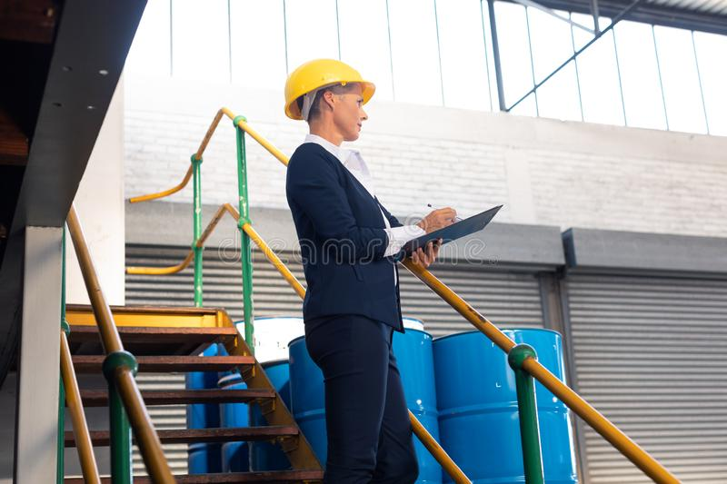 Female manager writing on clipboard on stairs in warehouse. Low angle view of Caucasian female manager writing on clipboard on stairs in warehouse. This is a royalty free stock photos