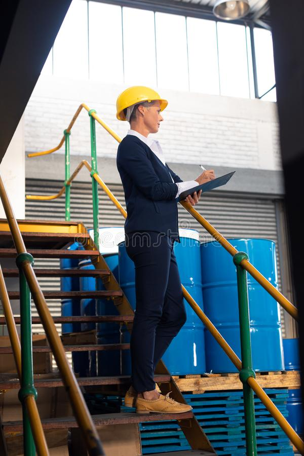 Female manager writing on clipboard on stairs in warehouse. Low angle view of Caucasian female manager writing on clipboard on stairs in warehouse. This is a stock image