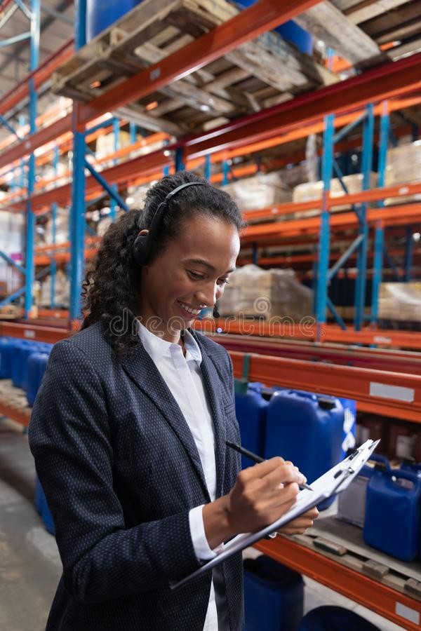 Female manager writing on clipboard while talking on headset in warehouse. African American female manager writing on clipboard while talking on headset in stock photos