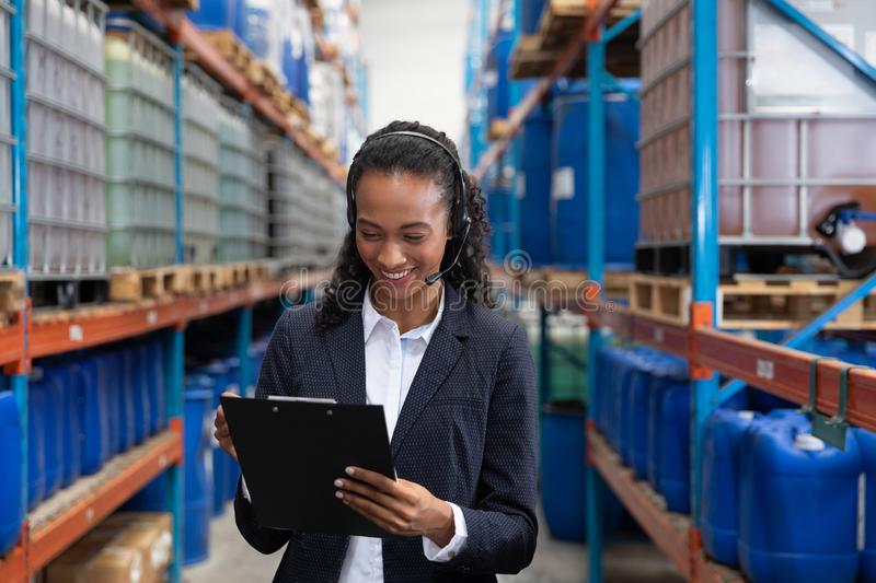Female manager writing on clipboard while talking on headset in warehouse. Happy female manager writing on clipboard while talking on headset in warehouse. This stock photos