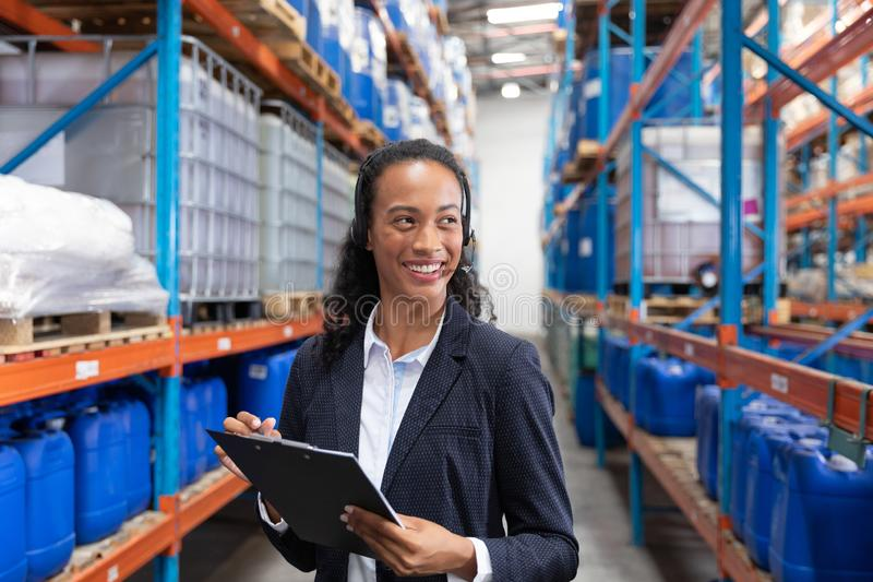 Female manager writing on clipboard while talking on headset in warehouse. Happy female manager writing on clipboard while talking on headset in warehouse. This royalty free stock photography