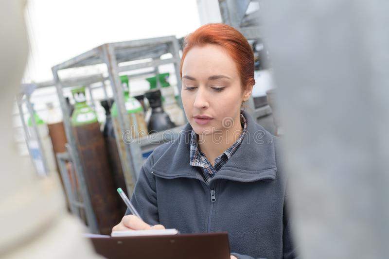 Female manager writing on clipboard in warehouse stock photo