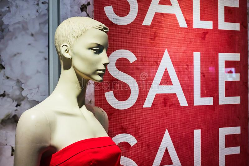 Female mannequin in a shop window on the background of the inscription sale.  stock photography