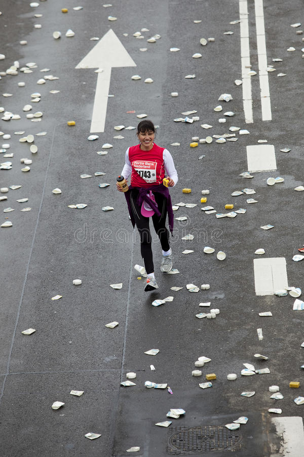 Female marathon runner lagging behind in Rott. Running over streets covered with trash from the refreshments, a woman is running on her own lagging behind in the stock photography