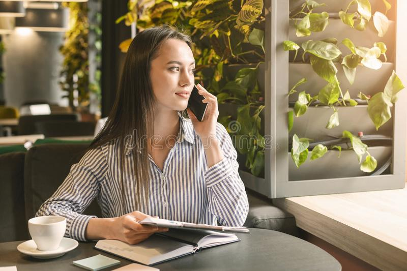 Female marketing manager making mobile negotiating in cafe royalty free stock image