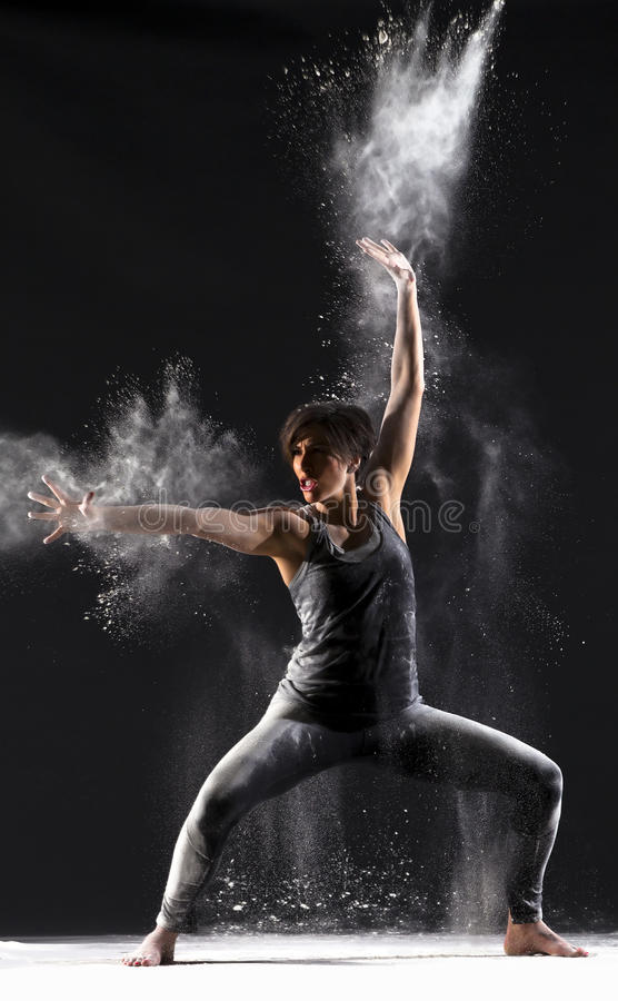 Female Martial Artist with Powder. Female martial artist with back lit powder showing explosive power and technique over black background stock photos
