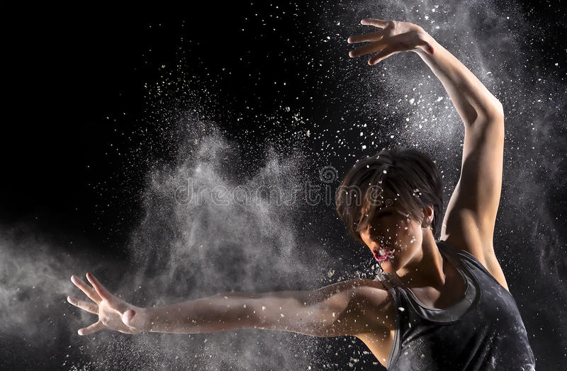 Female Martial Artist with Powder. Female martial artist with back lit powder showing explosive power and technique over black background royalty free stock photo