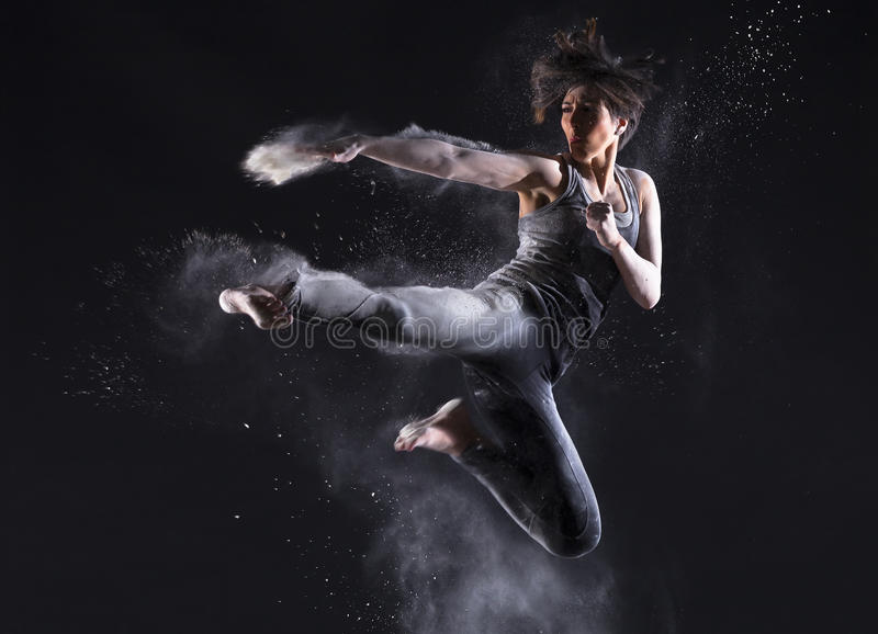 Female Martial Artist with Powder Jump Kick stock image