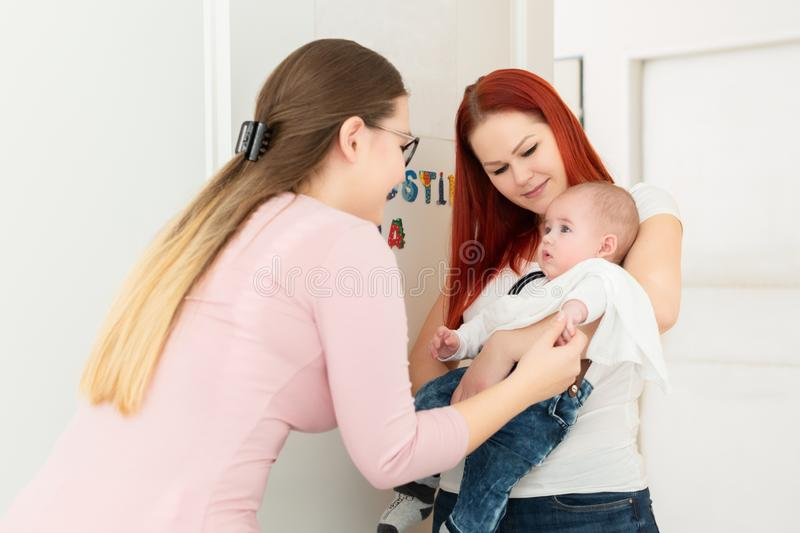 Female massage therapist or a doctor welcoming young mother and her infant son in her office. Baby massage concept. royalty free stock image