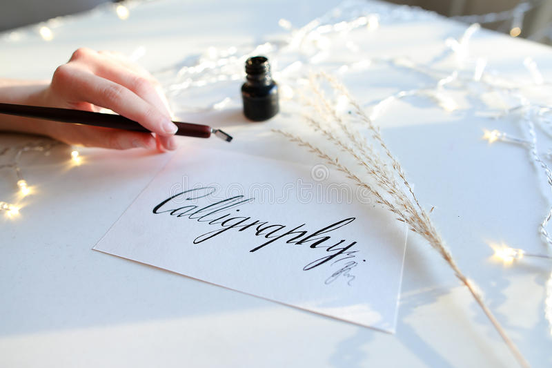 Female master of lettering of ink writes word on paper, sitting royalty free stock image