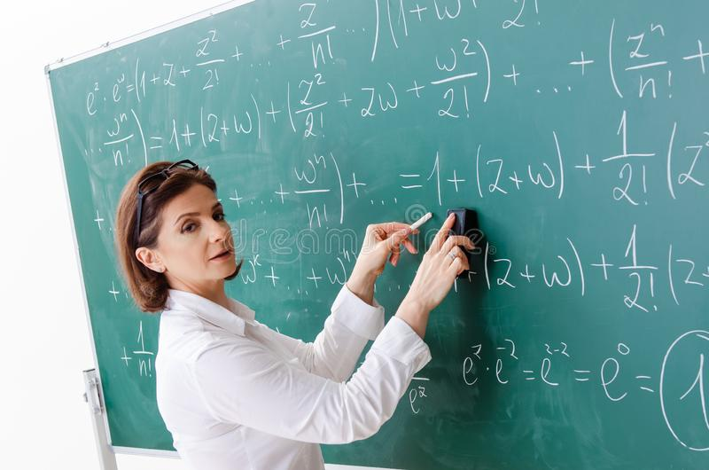 The female math teacher in front of the chalkboard royalty free stock photo