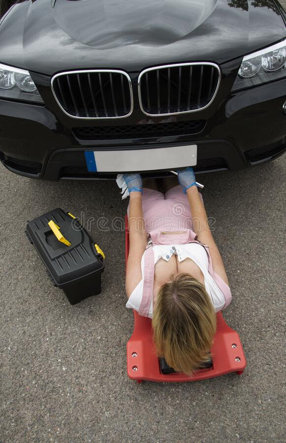 Female mechanic on a crawler to access underside of a automobile. royalty free stock photos