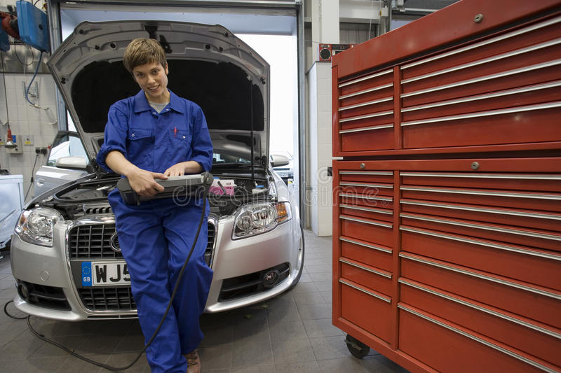 Female mechanic with diagnostic computer by open bonnet of car stock images