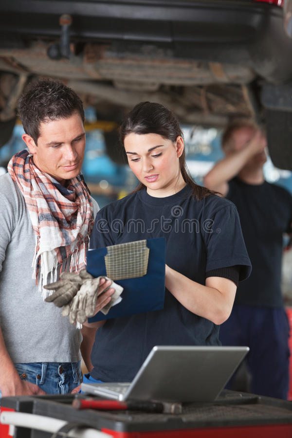 Download Female Mechanic Explaing Repairs To Client Stock Photo - Image: 20988948