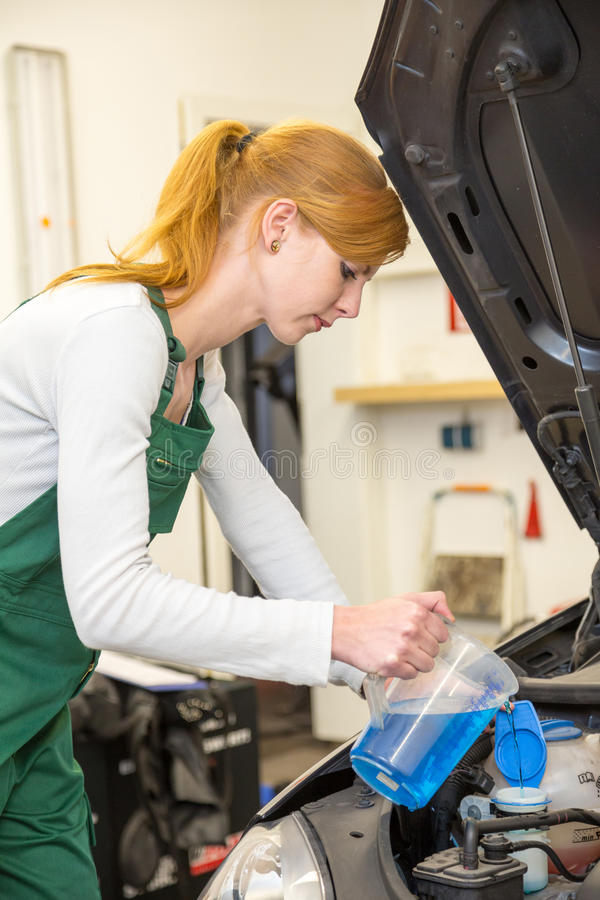 Female mechanic fills coolant or cooling fluid in motor of a car stock image