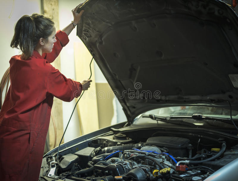 Female mechanic lifting hood of car royalty free stock image