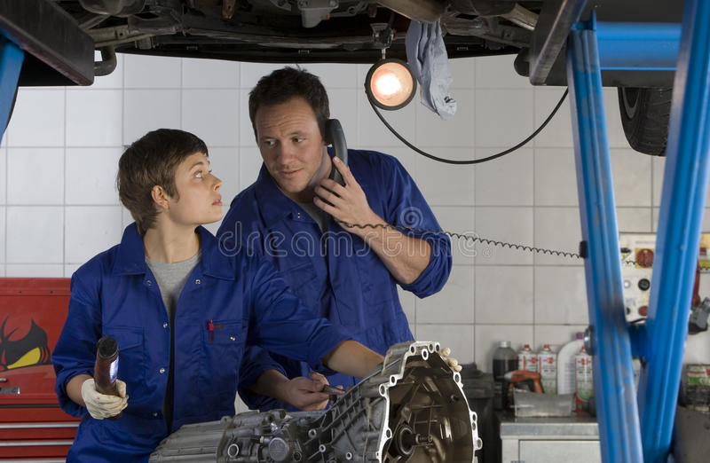 Female mechanic looking at colleague on telephone by engine of elevated car stock photo