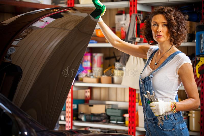 Female mechanic opening the hood of the car royalty free stock image