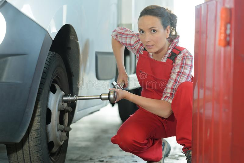 Female mechanic removing rim bolts royalty free stock image