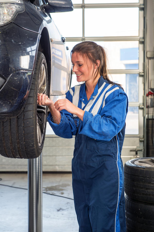 Female mechanic replacing vehicle tyres. Young female mechanic, removing the bolts of the front wheel of a vehicle on a car lift, wearing coveralls, replaicng stock photography