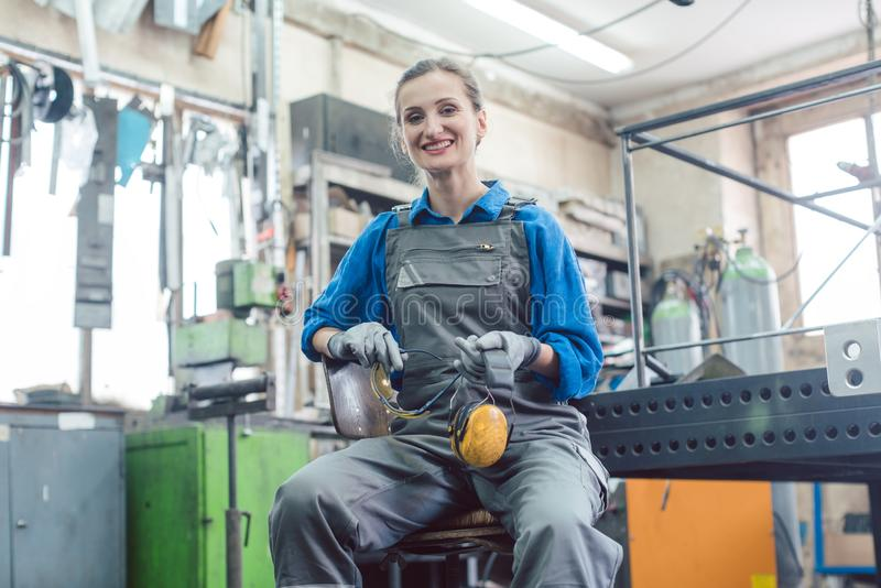 Female mechanic sitting in metal workshop looking into camera stock photos