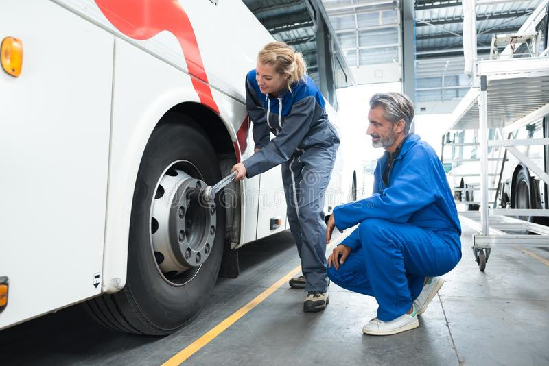 Female mechanic using tonque wrench on bus wheel nuts stock photography