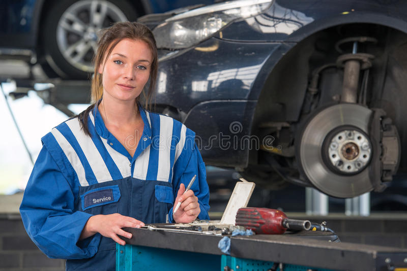 Female mechanic working on a MOT test. Female mechanic checking a car during a periodic technical service or MOT test royalty free stock image