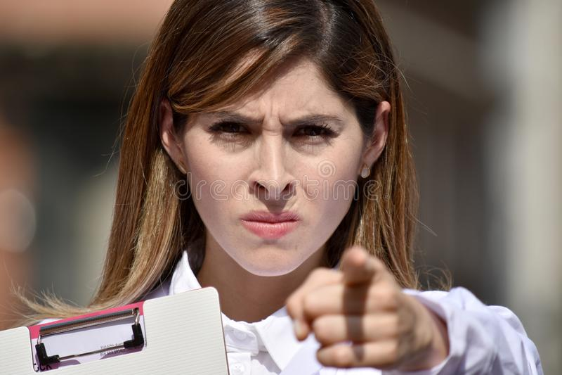 Female Medic Pointing Wearing Lab Coat With Clipboard. A pretty young Colombian adult female stock images
