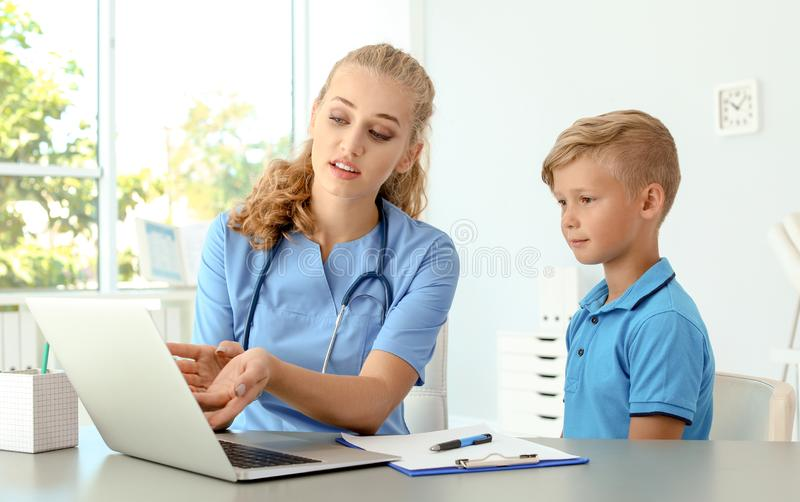 Female medical assistant explaining examination result to child in clinic stock image