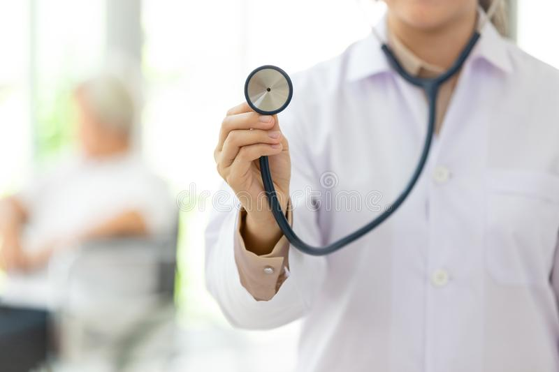 Female medical doctor holding stethoscope,senior people sitting in wheelchair as a background,closeup of hand young physician royalty free stock images