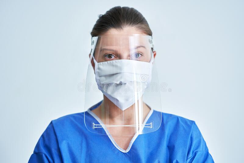 Portrait of female medical doctor wearing protective mask and face shield. Female medical doctor wearing protective mask and face shield royalty free stock photo