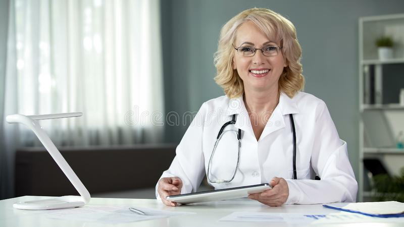 Female medical expert with tablet in hands smiling in camera, sitting cabinet. Stock photo stock photo