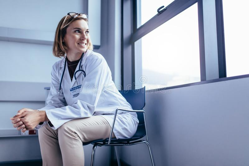 Female medical professional on chair in hospital ward royalty free stock photography