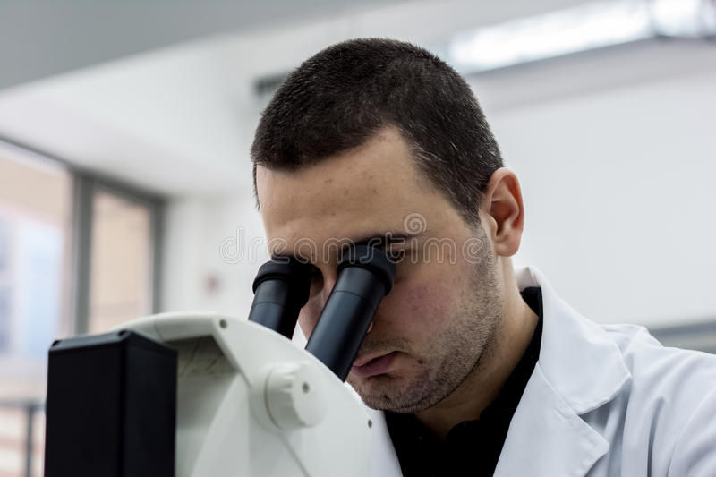Female medical or scientific researcher man doctor looking through a microscope in a laboratory. Young scientist doing some royalty free stock photo