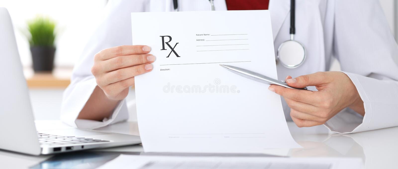 Female medicine doctor hand hold clipboard pad and give prescription to patient closeup. Panacea and life save royalty free stock photos