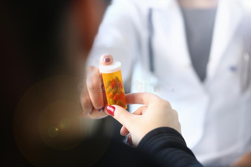 Female medicine doctor hand hold jar of pills and stock photo