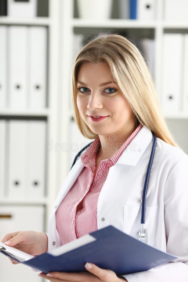 Beautiful smiling female doctor hold clipboard. Female medicine doctor hand hold jar of pills and write prescription to patient at worktable. Panacea and life stock photography