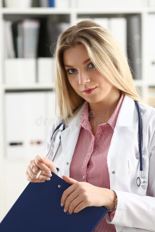 Beautiful smiling female doctor hold clipboard. Female medicine doctor hand hold jar of pills and write prescription to patient at worktable. Panacea and life royalty free stock images