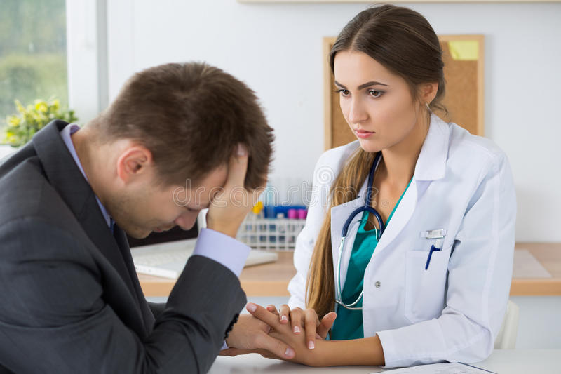 Female medicine doctor holding business man hand for encouragement stock photography