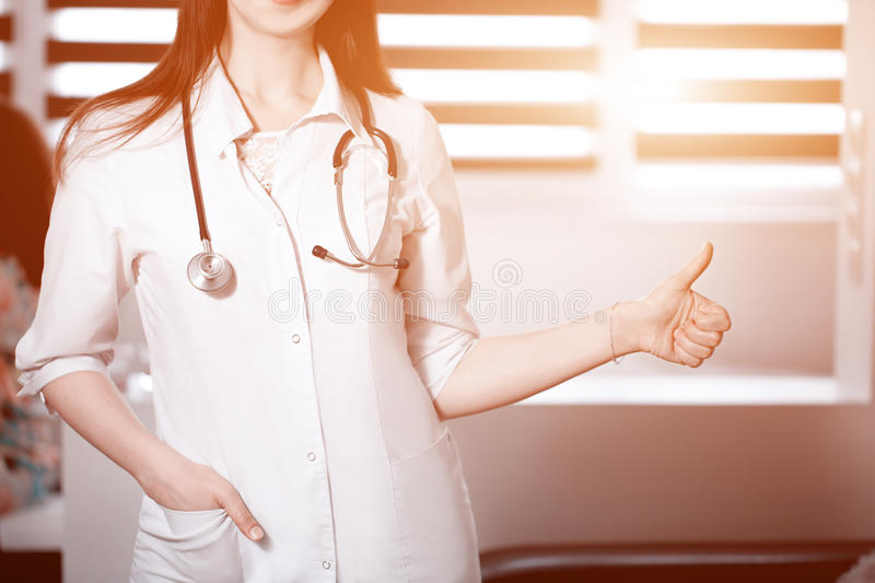 Female medicine doctor showing OK or approval sign with thumb up. High level and quality medical service, best treatment royalty free stock photo