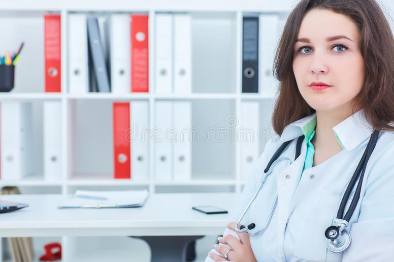 Young female medicine doctor standing with hands crossed on her chest and looking at the camera. Medical help or royalty free stock image