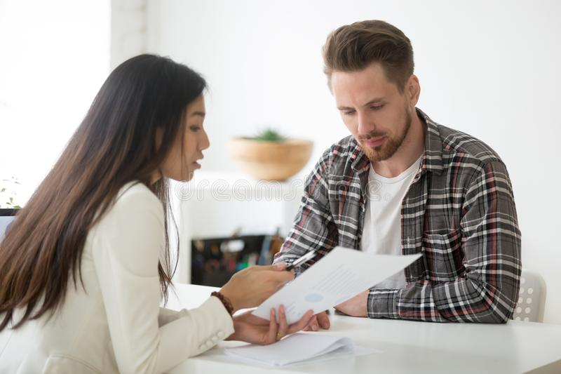 Female mentor coaching male employee on financial issues. Serious Asian businesswoman talking discussing financial statistics with coworker, mentor coaching male royalty free stock photos